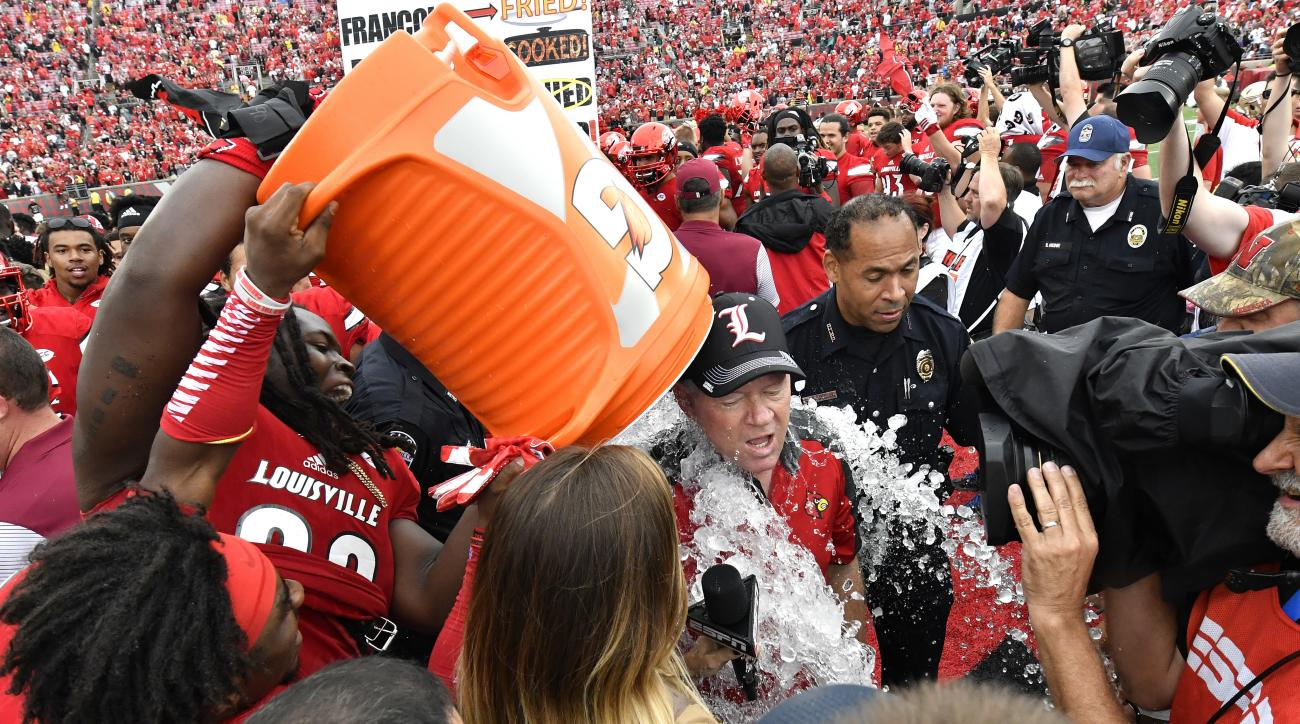 Louisville head coch Bobby Petrino gets the doused following Louisville's 63-20 victory over Florida State in an NCAA college football game, Saturday, Sep. 17, 2016 in Louisville, Ky. (AP Photo/Timothy D. Easley)