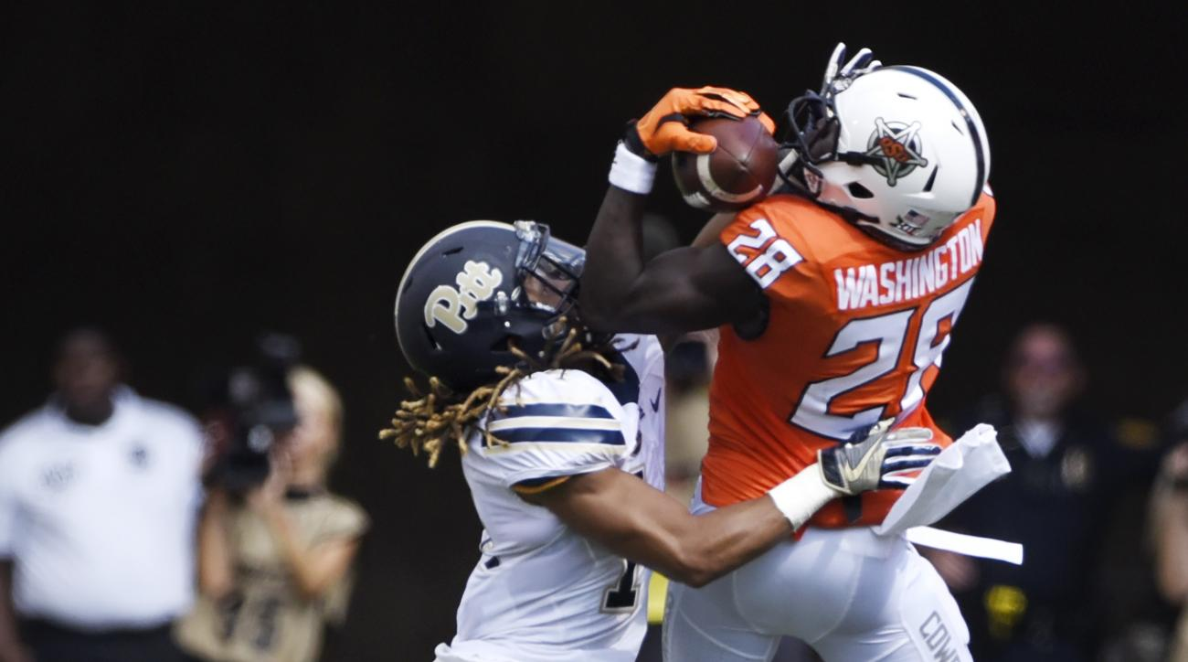 Oklahoma State wide receiver James Washington, right catches a pass while being tackled by Pittsburgh defensive back Avonte Maddox during the first half of an NCAA college football game in Stillwater, Okla., Saturday, Sept. 17, 2016.(AP Photo/Brody Schmid