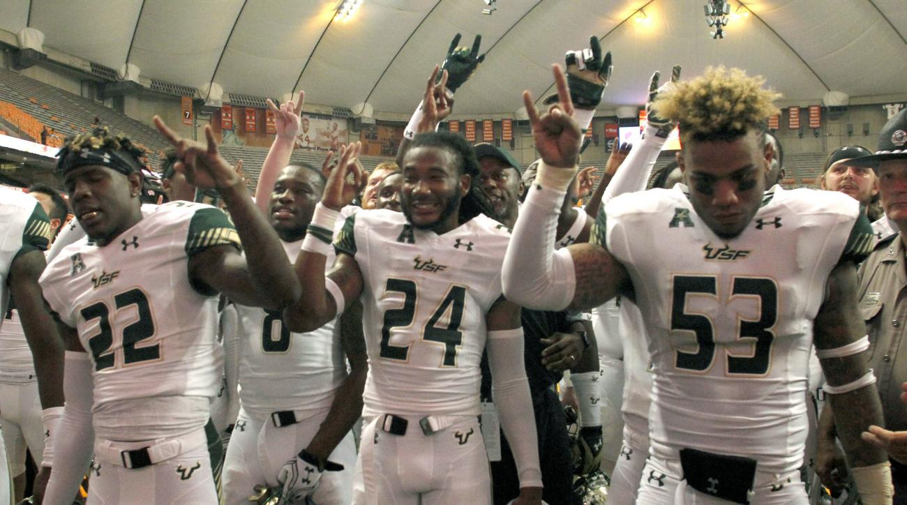 South Florida's Hassan Childs, left, Johnny Ward, center, and Danny Thomas, right, celebrate after an NCAA college football game against Syracuse in Syracuse, N.Y., Saturday, Sept. 17, 2016. South Florida won 45-20. (AP Photo/Nick Lisi)