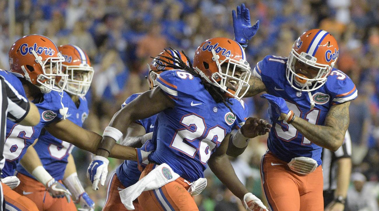 Florida defensive back Marcell Harris (26) is congratulated by defensive back Quincy Wilson (6) and defensive back Teez Tabor (31) after Harris intercepted a pass during the first half of an NCAA college football game against North Texas in Gainesville, F