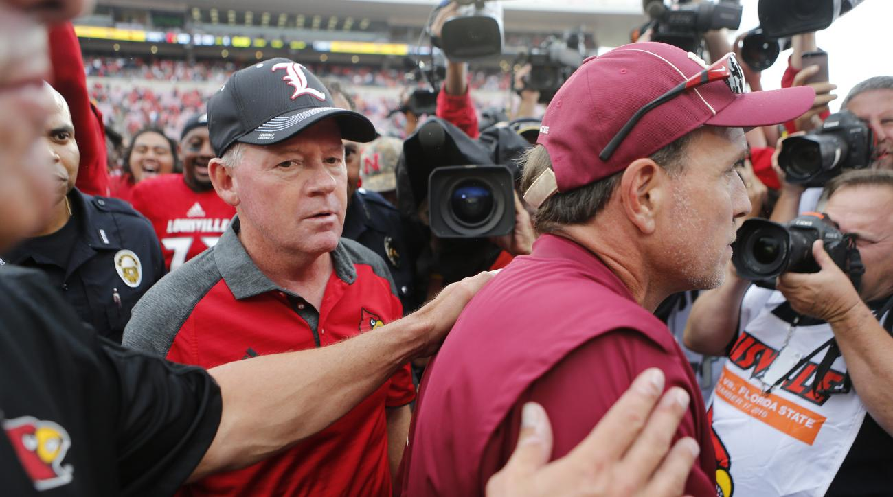 In this Saturday, Sept. 17, 2016, photo, Florida State coach Jimbo Fisher, right, walks away after meeting with Louisville coach Bobby Petrino, center, at the end of an NCAA college football game in Louisville, Ky. Louisville won, 63-20. (Pat McDonogh/The
