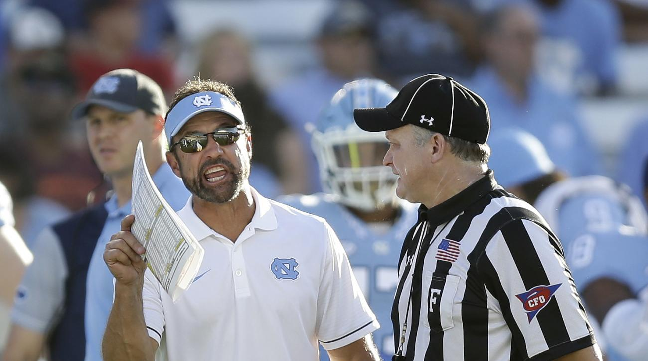 FILE - In this Sept. 17, 2016, file photo, North Carolina head coach Larry Fedora, left, argues with an official in the second half of an NCAA college football game against James Madison,  in Chapel Hill, N.C. Fedora is trying to solve a penalty problem e