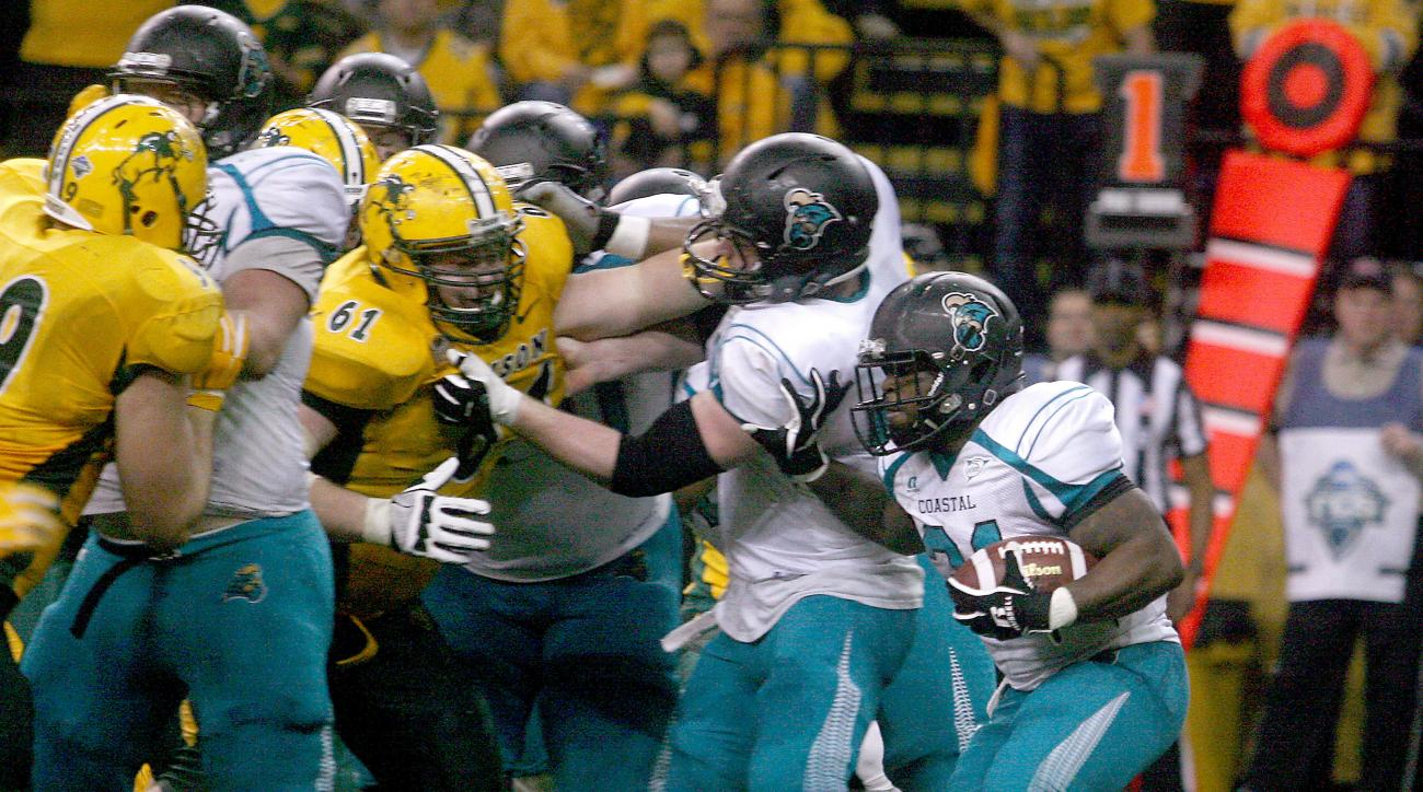 FILE - In this Dec. 13, 2014, file photo, Coastal Carolina back De'Angelo Henderson, right, looks for running room against the North Dakota State defense during an FCS quarterfinal NCAA college football game in Fargo, N.D. Its almost a sure thing that Coa