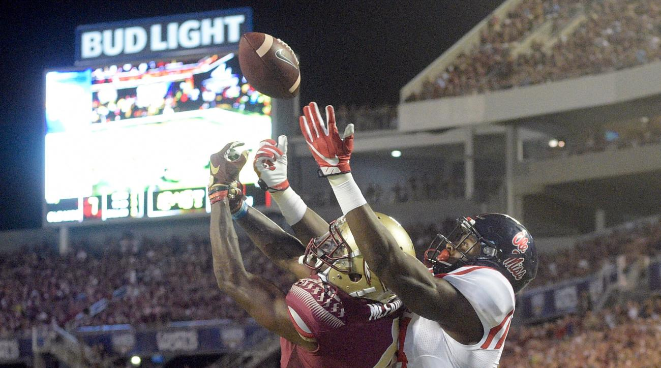 File-This Sept. 5, 2016, file photo shows Mississippi wide receiver D.K. Metcalf, right, catching a pass over Florida State defensive back Tarvarus McFadden for a touchdown during the first half of an NCAA college football game in Orlando, Fla. (AP Photo/