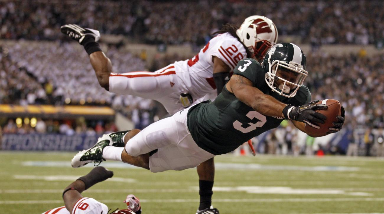 File-This Dec. 3, 2011, file photo shows Michigan State's B.J. Cunningham (3) diving into the end zone for a touchdown in front of Wisconsin's Antonio Fenelus during the Big Ten conference championship NCAA college football game , in Indianapolis.  The ei