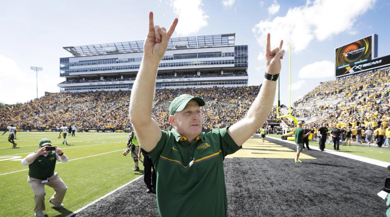 FILE - In this Saturday, Sept. 17, 2016, file photo, North Dakota State head coach Chris Kileman gestures to fans after  they defeated Iowa 23-21 in an NCAA college football game against Iowa, in Iowa City, Iowa. AP Photo/Charlie Neibergall, File)