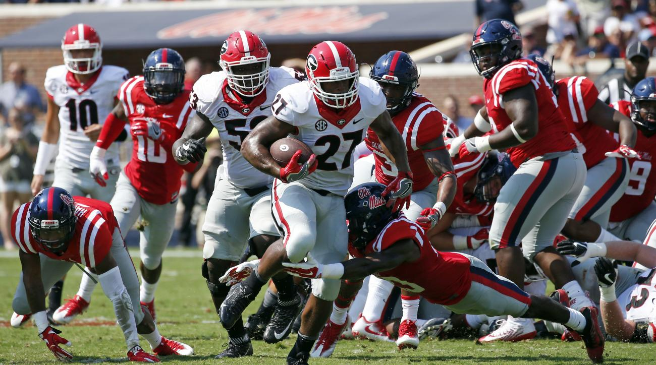 Georgia running back Nick Chubb (27) attempts to run from a surging Mississippi defense during the first half of an NCAA college football game, Saturday, Sept. 24, 2016, in Oxford, Miss. (AP Photo/Rogelio V. Solis)