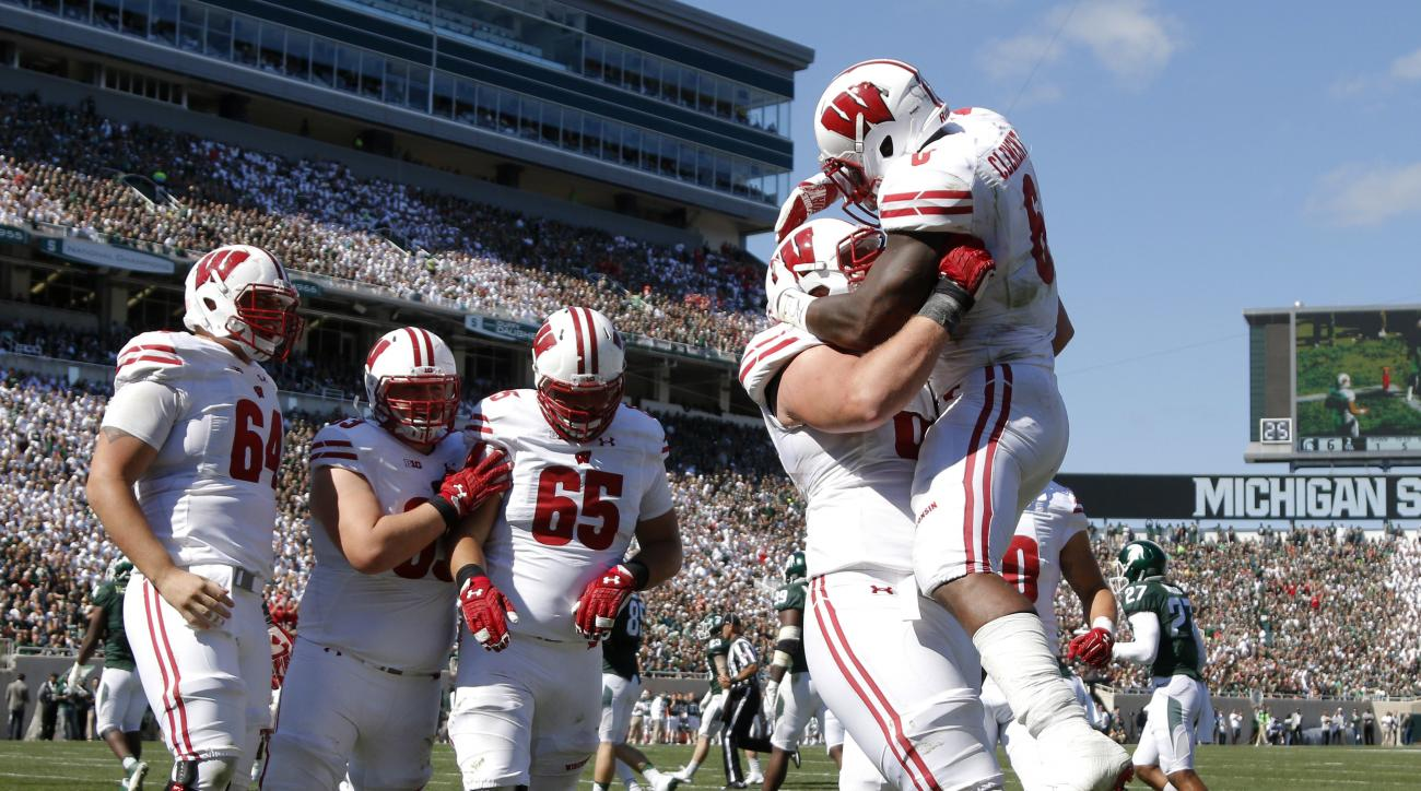 Wisconsin's Corey Clement, right, celebrates his touchdown against Michigan State with teammates, from left, Brett Connors, Michael Deiter, Olive Sagapolu (65) and Beau Benzschawel during the third quarter of an NCAA college football game, Saturday, Sept.