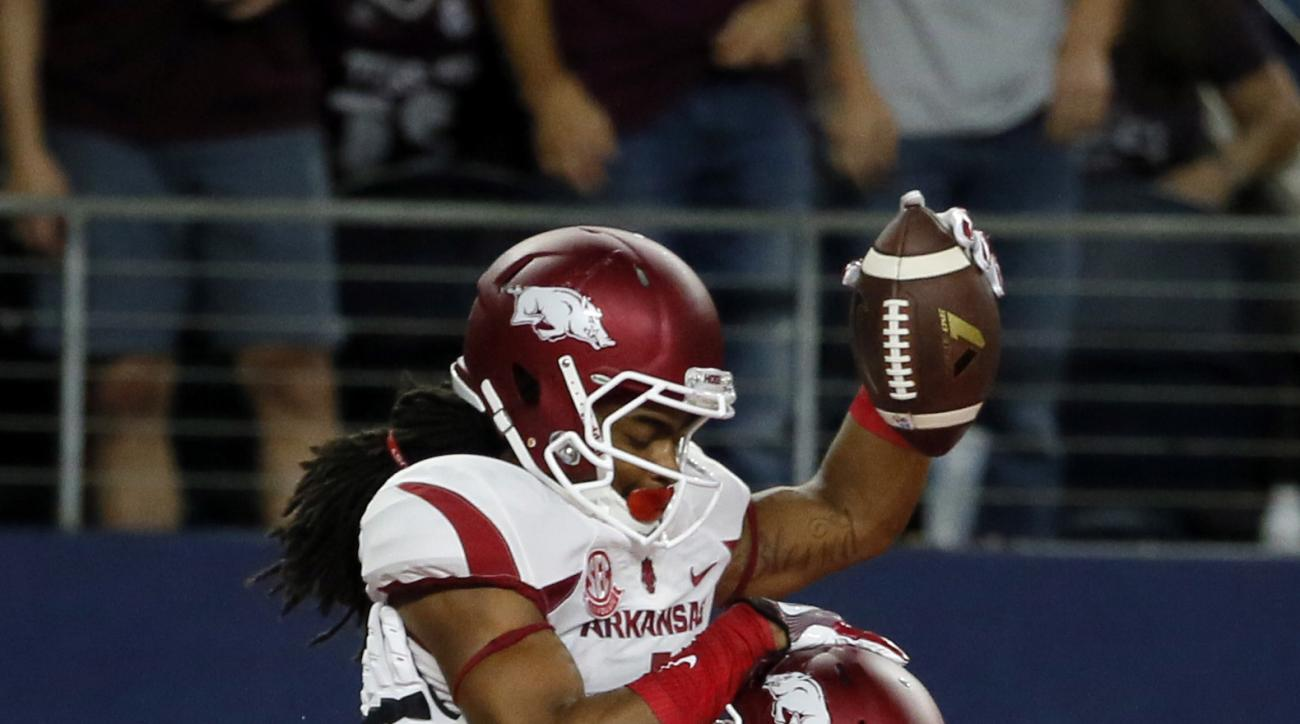 Arkansas wide receiver Dominique Reed (3) and offensive lineman Dan Skipper (70) celebrate with Keon Hatcher, top, after Hatcher caught a pass for a touchdown during the first half of an NCAA college football game against Texas A&M on Saturday, Sept. 24,