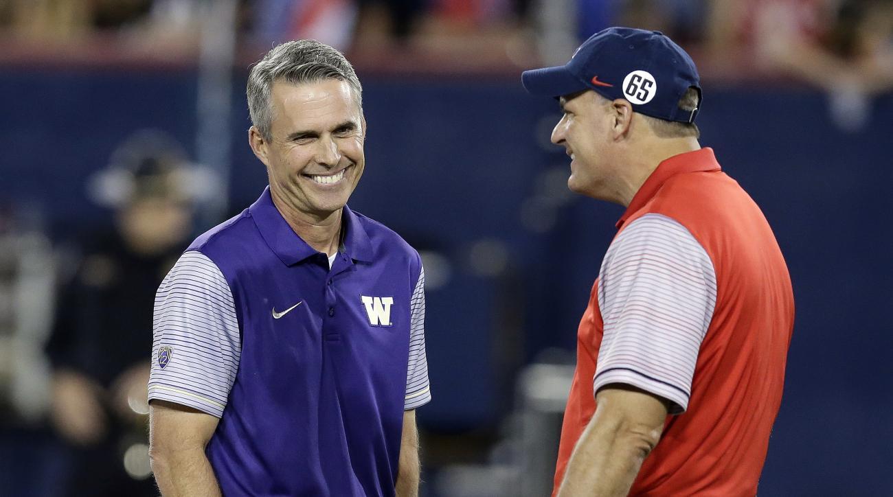 Washington coach Chris Petersen, left, talks to Arizona coach Rich Rodriguez before an NCAA college football game, Saturday, Sept. 24, 2016, in Tucson, Ariz. (AP Photo/Rick Scuteri)