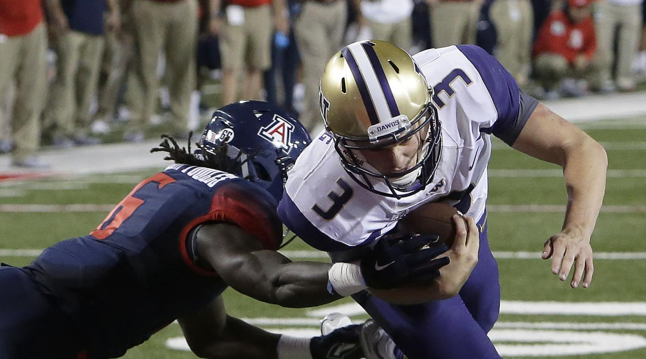Washington quarterback Jake Browning (3) dives into the end zone with Arizona safety Demetrius Flannigan-Fowles hanging on during the second half of an NCAA college football game, Saturday, Sept. 24, 2016, in Tucson, Ariz. Washington defeated Arizona 35-2