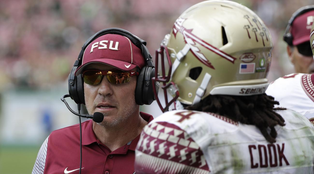 In this Saturday, Sept. 24, 2016, photo, Florida State head coach Jimbo Fisher talks to running back Dalvin Cook during the third quarter of an NCAA college football game against South Florida in Tampa, Fla. After firing the most successful coach football