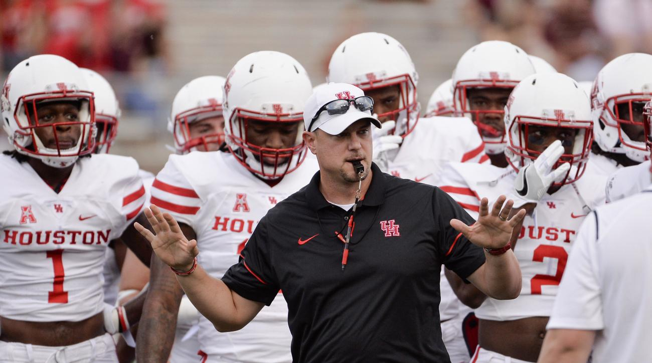 FILE - In this Saturday, Sept. 24, 2016, file photo, Houston head coach Tom Herman runs drills with his team before an NCAA college football game against Texas State in San Marcos, Texas. After firing the most successful coach football coach in the histor