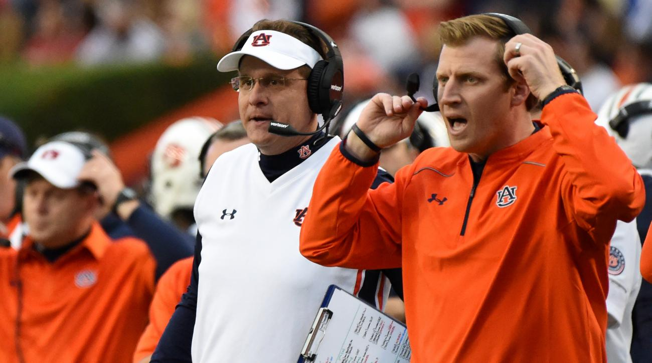 FILE - In this Nov. 21, 2015, file photo, Auburn coach Gus Malzahn, left, and offensive coordinator Rhett Lashlee, right, watch the action against Idaho during the first half of an NCAA football game in Auburn, Ala.  Malzahn, who built his career on offen