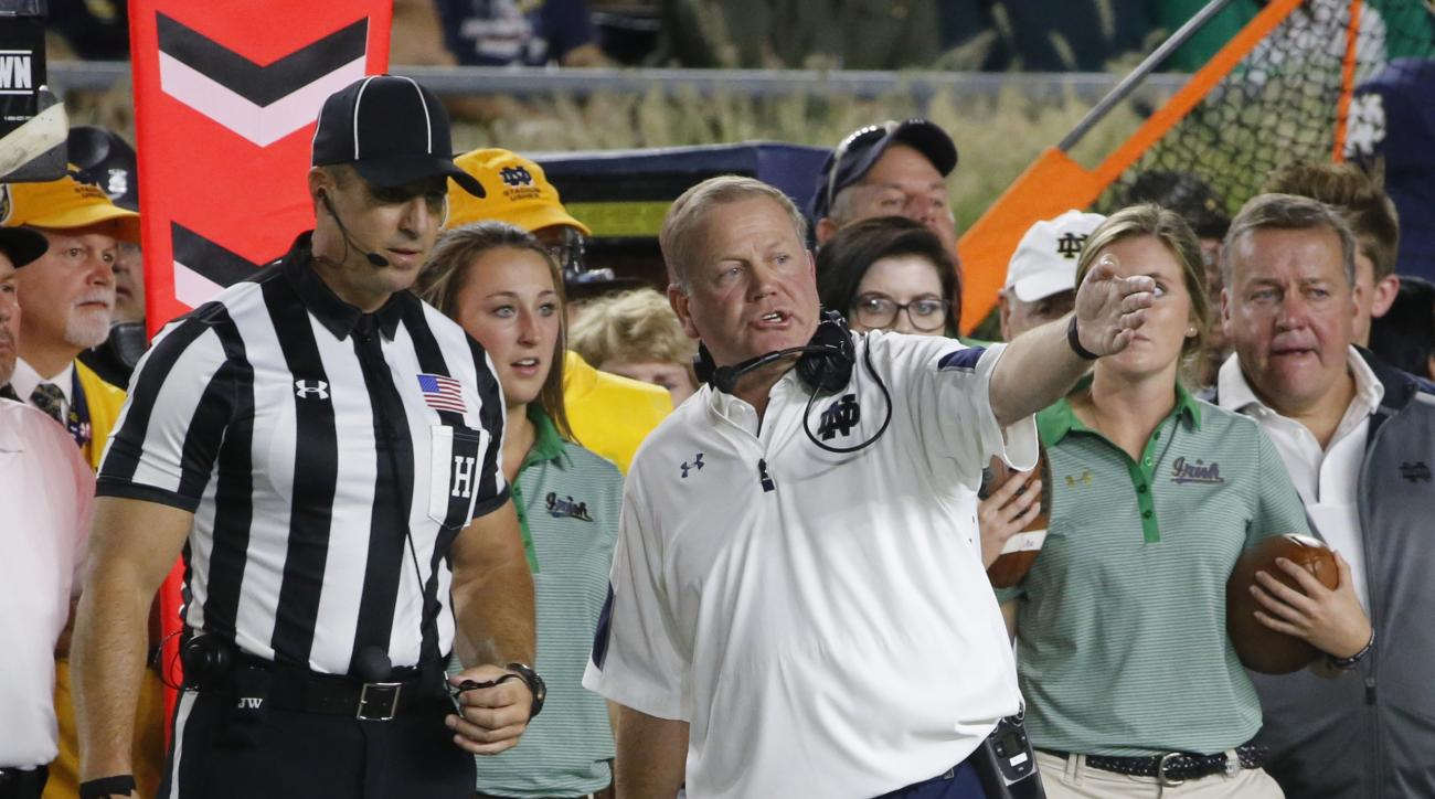 FILE - In this Saturday, Sept. 17, 2016, file photo, Notre Dame head coach Brian Kelly, right, talks to an official during the first half of an NCAA college football game against Michigan State in South Bend, Ind. Kelly is promising more passion from his