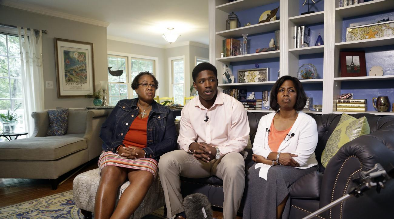 Allen Artis, center, speaks with members of the media alongside his mother Stephanie Artis, right, and his aunt Dr. Avis Artis Tuesday, Sept. 27, 2016 in Durham, N.C. Artis, a North Carolina football player facing charges of sexual battery and assault on