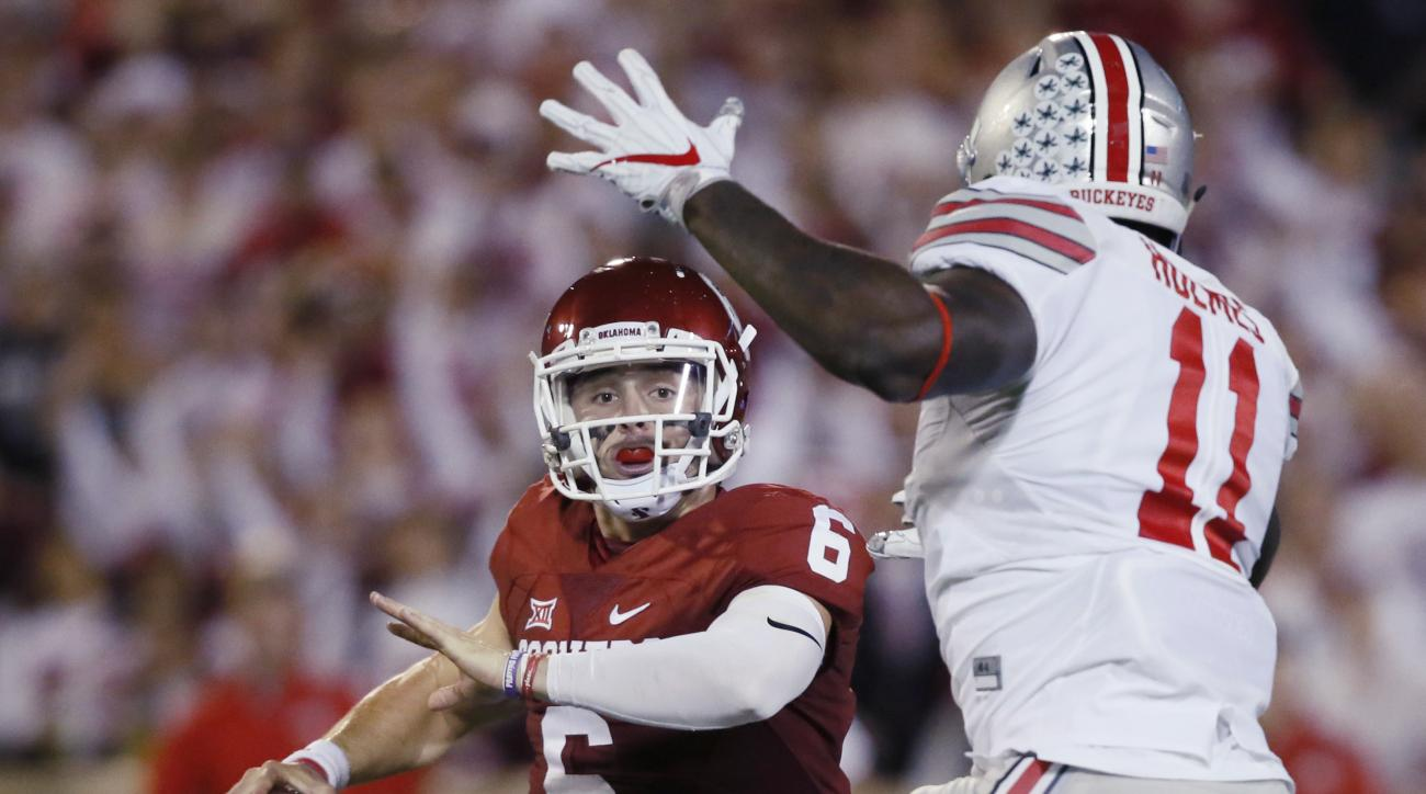 FILE - In this Sept. 17, 2016, file photo, Oklahoma quarterback Baker Mayfield (6) is pressured by Ohio State defensive end Jalyn Holmes (11) during an NCAA college football game in Norman, Okla. Oklahoma faces TCU in a Big 12 game this week. (AP Photo/Su