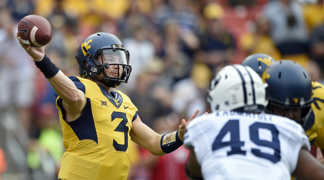 FILE - In this Sept. 24, 2016, file photo, West Virginia quarterback Skyler Howard (3) passes while pressured by BYU defensive lineman Moses Kaumatule (49) during the first half of an NCAA college football game Landover, Md. The Mountaineers host Kansas S