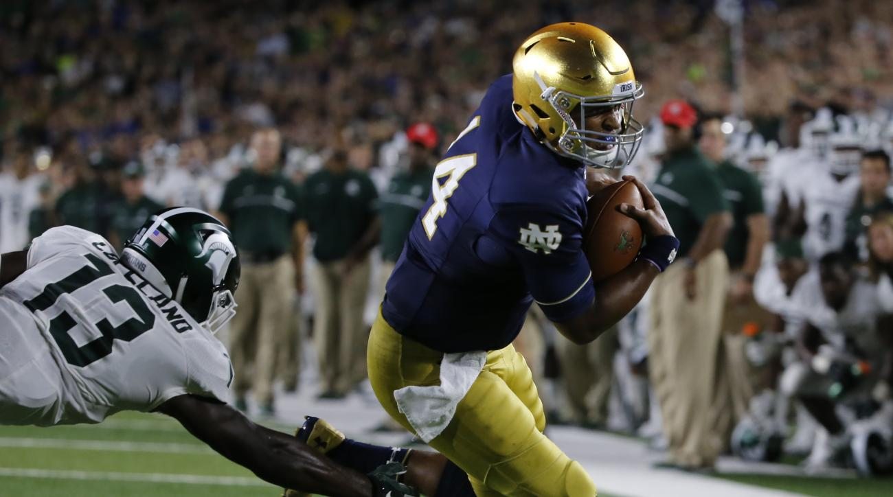 FILE - In this Sept. 17, 2016, file photo, Notre Dame quarterback DeShone Kizer (14) turns the corner past Michigan State cornerback Vayante Copeland (13) and heads to the end zone for a touchdown during the first half of an NCAA college football game aga