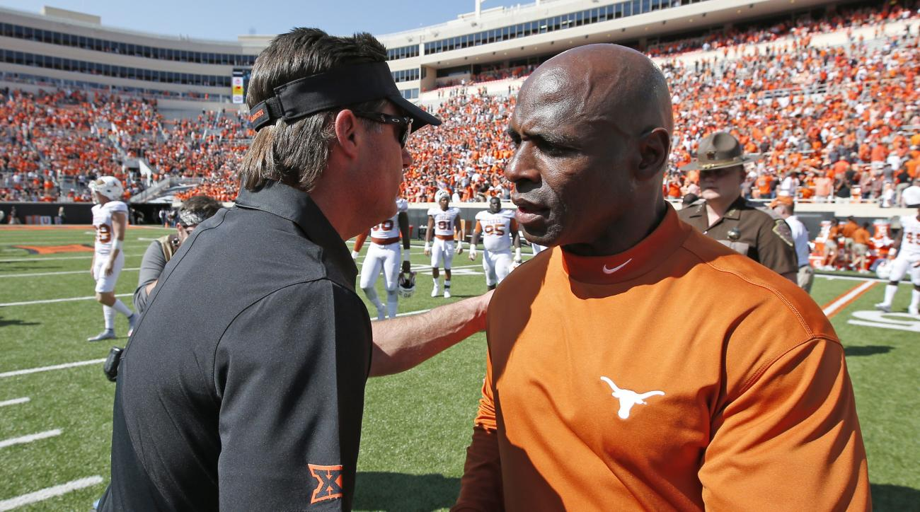 Oklahoma State head coach Mike Gundy, left, shakes hands with Texas head coach Charlie Strong, right, following an NCAA college football game in Stillwater, Okla., Saturday, Oct. 1, 2016. Oklahoma State won 49-31. (AP Photo/Sue Ogrocki)