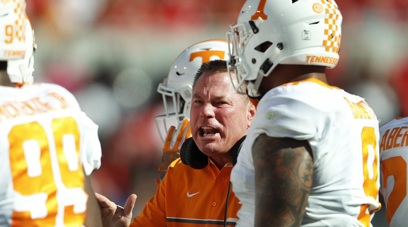 Tennessee head coach Butch Jones talks to his players in the first half of an NCAA college football game against  Georgia  Saturday, Oct. 1, 2016, in Athens, Ga. (AP Photo/John Bazemore)
