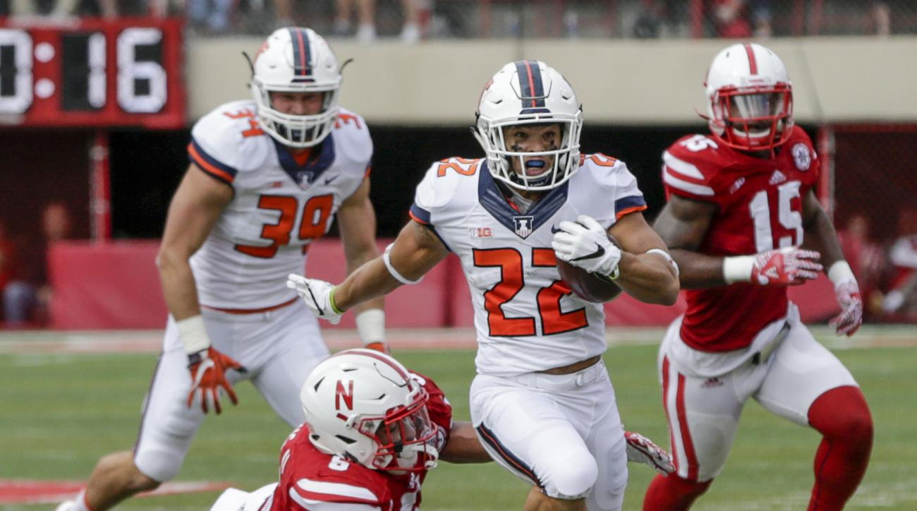 Illinois running back Kendrick Foster (22) runs for a touchdown away from a tackle attempt by Nebraska linebacker Dedrick Young II (5) and linebacker Michael Rose-Ivey (15) during the first half of an NCAA college football game in Lincoln, Neb., Saturday,
