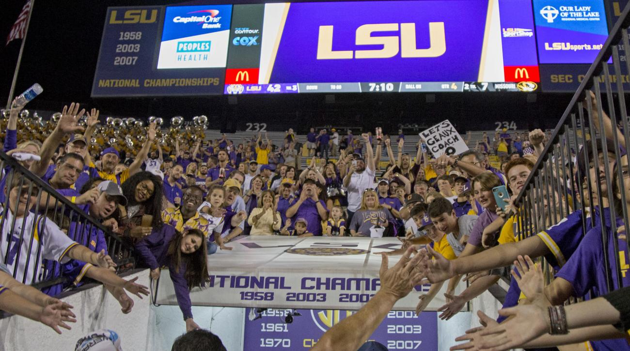 LSU interim coach Ed Orgeron touches hands with the crowd as he leaves Tiger Stadium after an NCAA college football game against Missouri in Baton Rouge, La., Saturday, Oct. 1, 2016. LSU won 42-7. (AP Photo/Max Becherer)