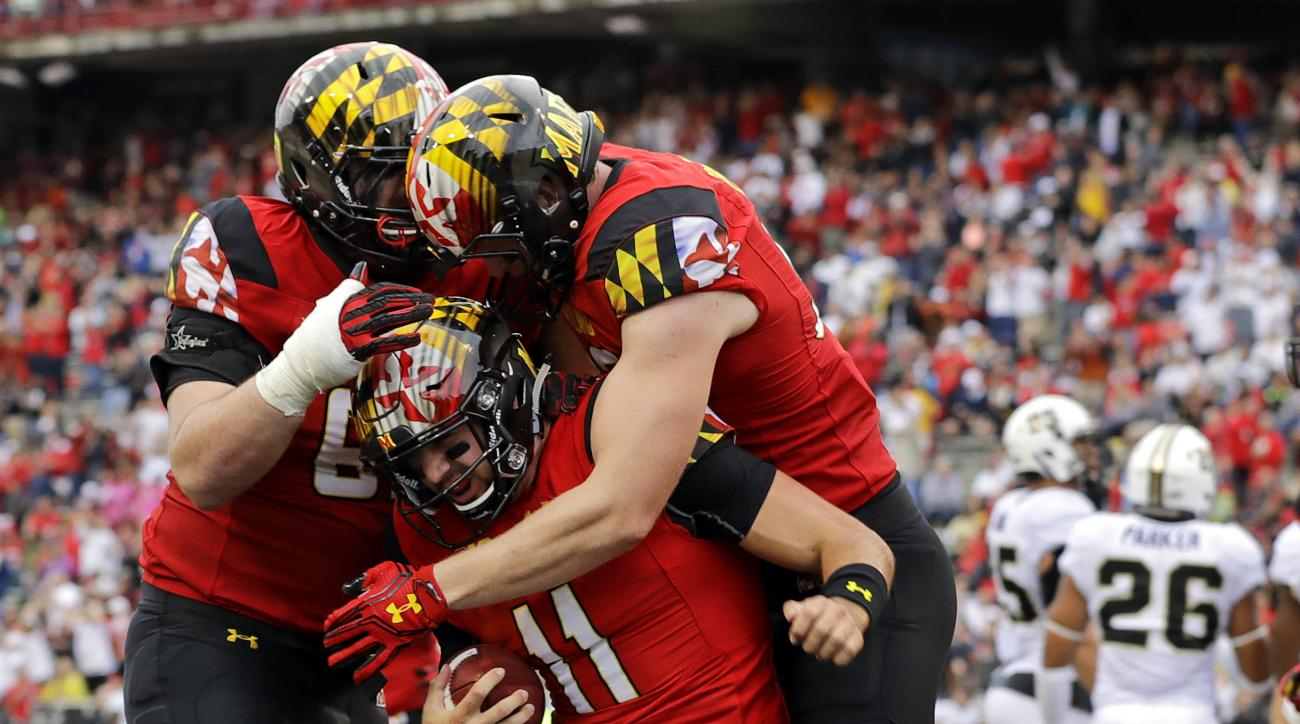 FILE - In this Saturday, Oct. 1, 2016, file photo, Maryland quarterback Perry Hills (11) celebrates his touchdown with teammates Mike Minter, left, and Avery Edwards in the first half of an NCAA college football game against Purdue in College Park, Md. Co
