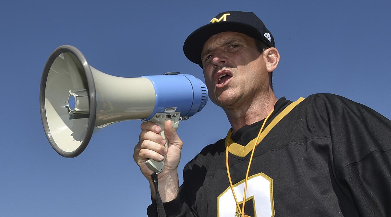 FILE - In this June 8, 2016, file photo, Michigan football coach Jim Harbaugh encourages high school football players in their speed drill at a Michigan Satellite Camp at Pearl High School in Pearl, Miss. Plenty of coaches use Twitter, whether theyre capi