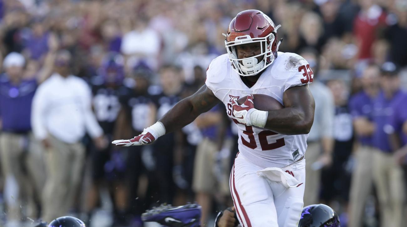 FILE - In this Oct. 1, 2016, file photo, Oklahoma running back Samaje Perine (32) runs with the ball during the first half of an NCAA college football game against TCU, in Fort Worth, Texas. Big 12 defenses are suffering every week. Eight of the leagues 1