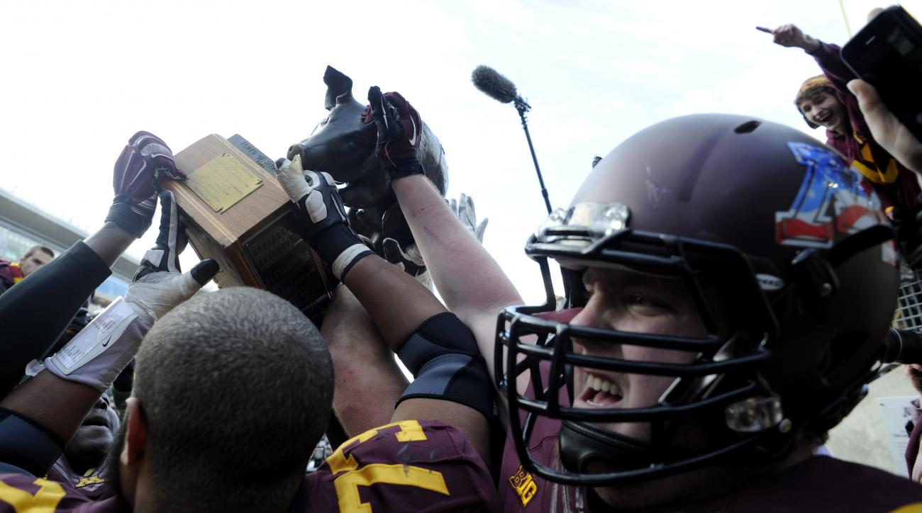 FILE - In this Nov. 8, 2014, file photo, Minnesota offensive lineman Joe Bjorklund (73) and offensive lineman Kyle McAvoy (71) hoist the Floyd of Rosedale trophy after their 51-14 win in an NCAA college football game against Iowa, in Minneapolis. Iowa at