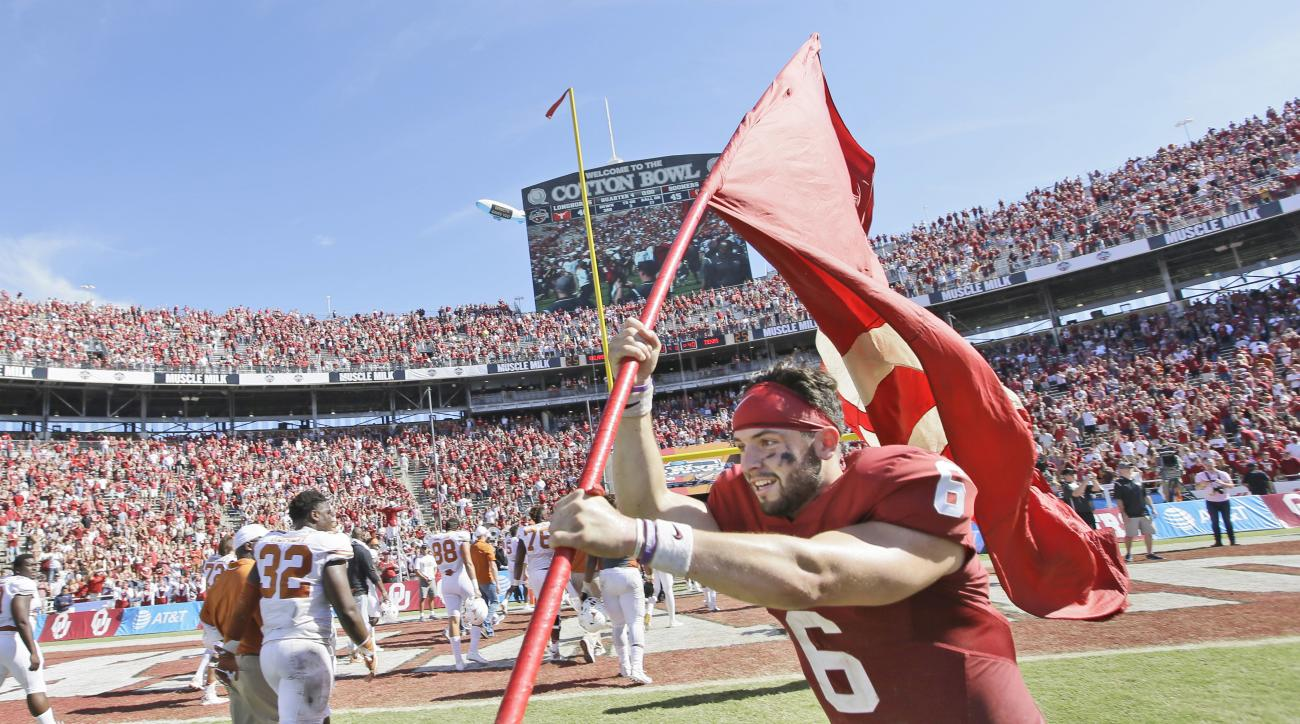 Oklahoma quarterback Baker Mayfield (6) runs on the field with a school flag after 45-40 win over Texas in an NCAA college football game\ in Dallas Saturday, Oct. 8, 2016. (AP Photo/LM Otero)