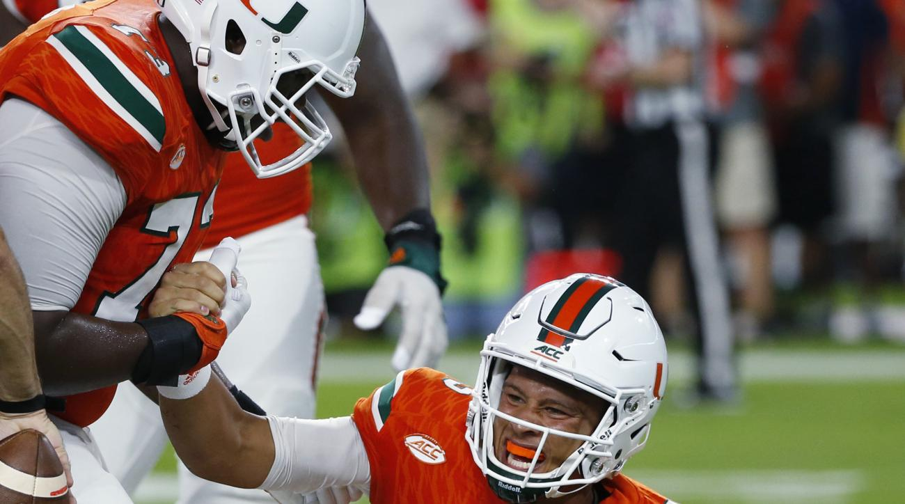 Miami Hurricanes quarterback Brad Kaaya (15) is helped to his feet after he was sacked during the first half of an NCAA college football game against the Florida State Seminoles, Saturday, Oct. 8, 2016, in Miami Gardens, Fla. (AP Photo/Wilfredo Lee)