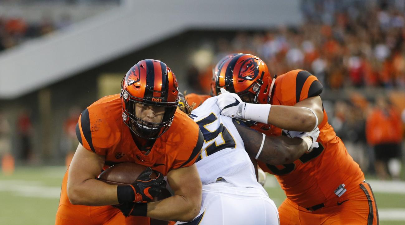 Oregon State running back Ryan Nall, left, breaks through the California defense to score a touchdown during the first half of an NCAA college football game in Corvallis, Ore., on Saturday, Oct. 8, 2016. (AP Photo/Timothy J. Gonzalez)