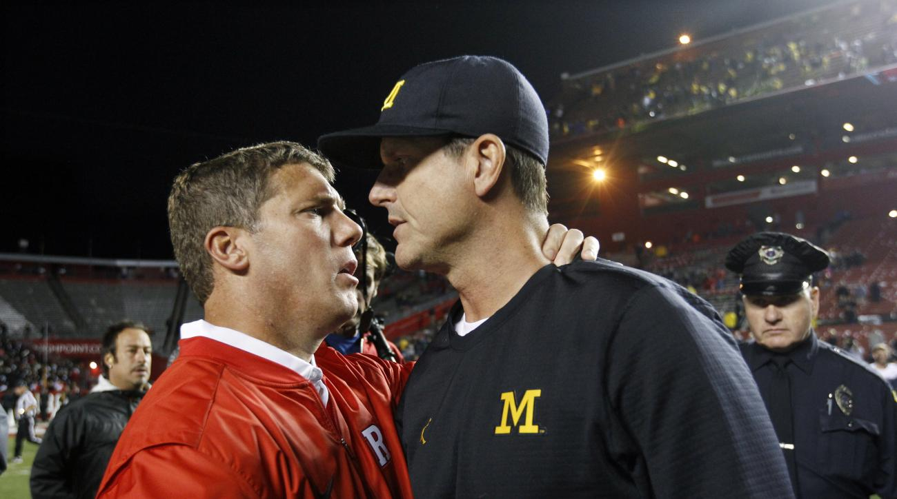 Michigan head coach Jim Harbaugh, right, greets Rutgers head coach Chris Ash at the end of an NCAA college football game Saturday, Oct. 8, 2016, in Piscataway, N.J. (AP Photo/Mel Evans)