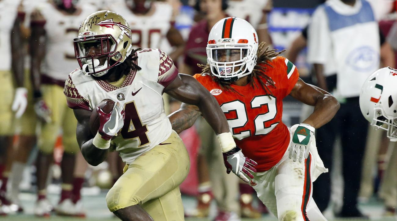 Florida State running back Dalvin Cook (4) carries the ball ahead of Miami defensive back Sheldrick Redwine (22) during the second half of an NCAA college football game, Saturday, Oct. 8, 2016, in Miami Gardens. (AP Photo/Wilfredo Lee)