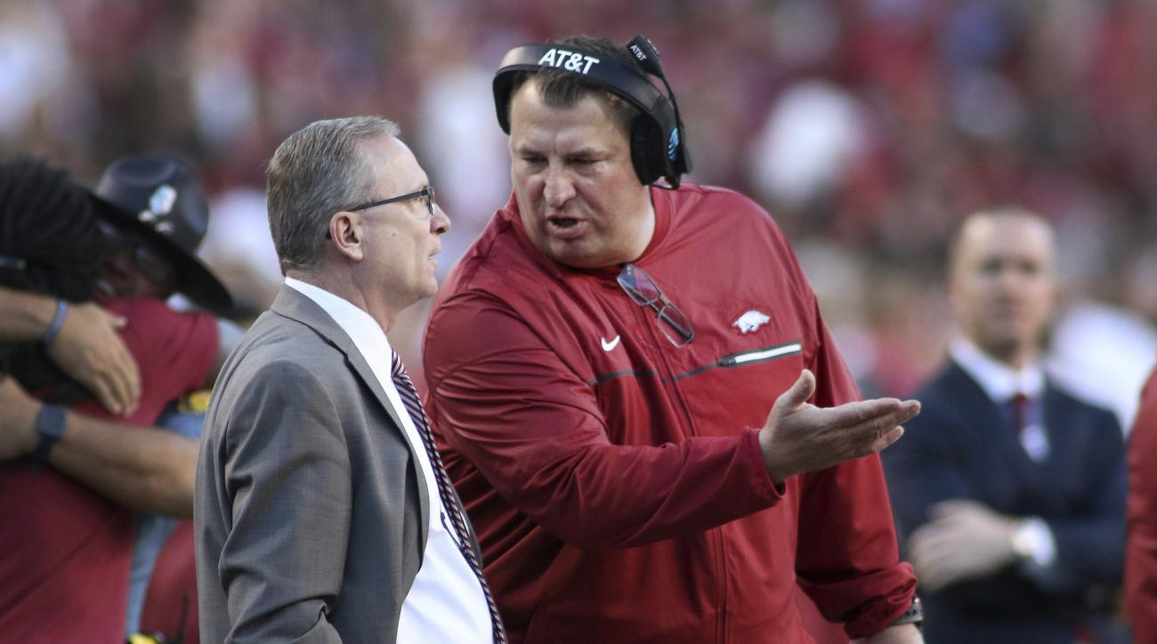 Arkansas coach Bret Bielema, right, talks to Athletic Director Jeff Long while officials review a play during the first quarter of Arkansas' NCAA college football game against Alabama on Saturday, Oct. 8, 2016, in Fayetteville, Ark. Alabama won 49-30. (AP