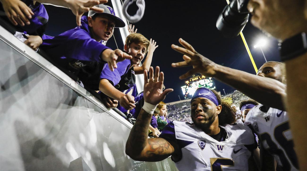 Washington linebacker Joe Mathis (5) greets fans at an NCAA college football game Saturday, Oct. 8, 2016, in Eugene, Ore. Washington defeated Oregon 70-21. (AP Photo/Thomas Boyd)