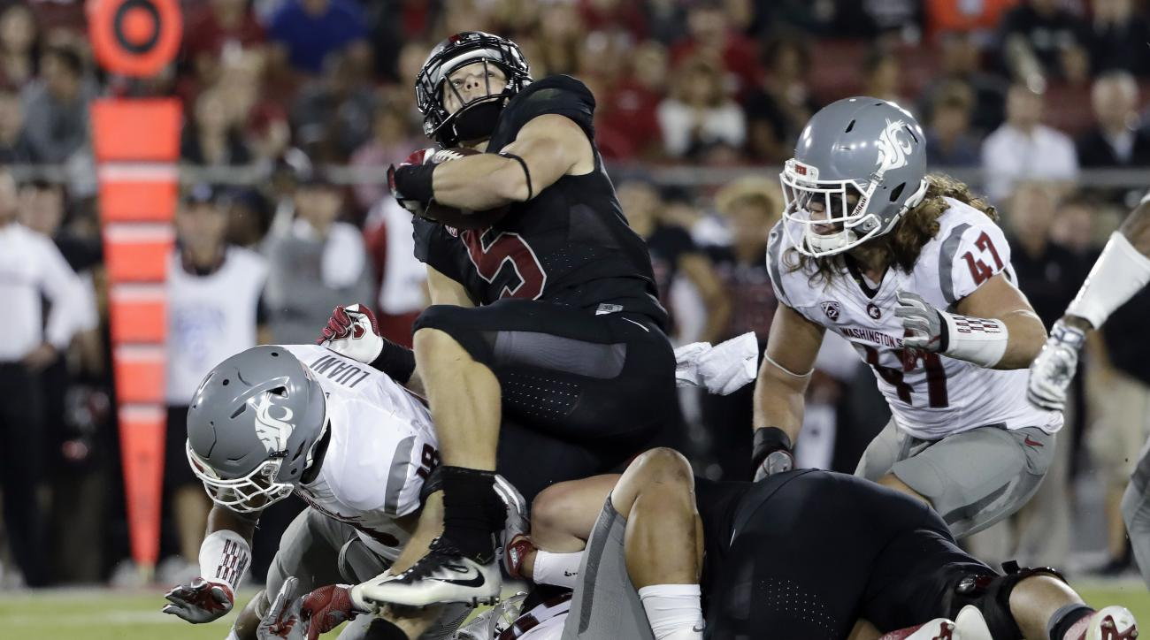 Stanford 's Christian McCaffrey (5) is stopped by a group of Washington State defenders during the first half of an NCAA college football game Saturday, Oct. 8, 2016, in Stanford, Calif. (AP Photo/Marcio Jose Sanchez)