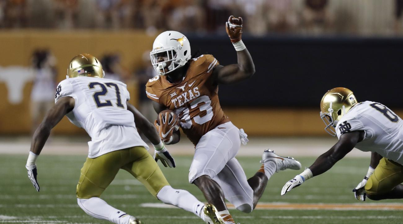 FILE - In this Sept. 4, 2016, file photo, Texas running back D'Onta Foreman (33) runs as Notre Dame cornerback Julian Love (27) pursues during the second half of an NCAA college football game in Austin, Texas. There are several different running combos in