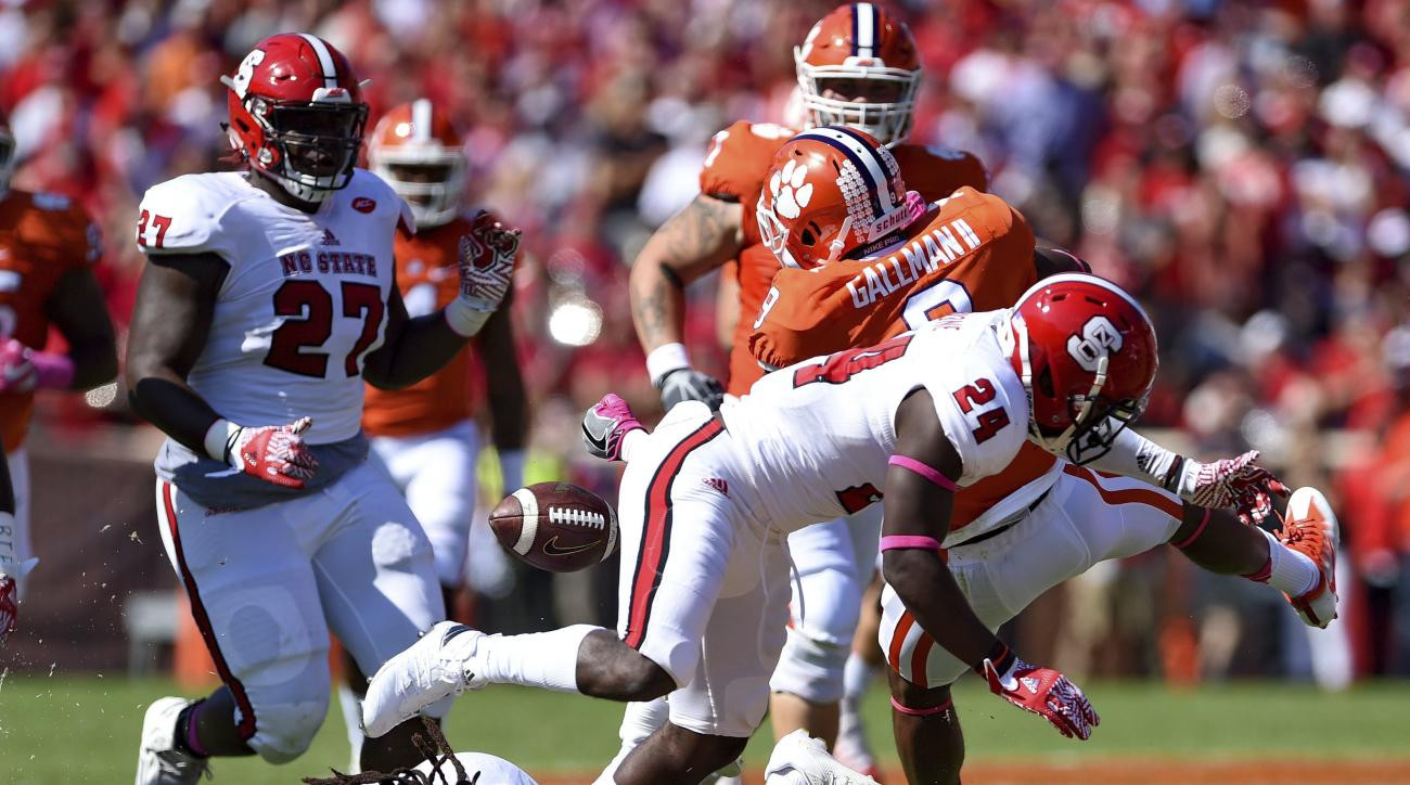 North Carolina State's Shawn Boone (24) tackles Clemson's Wayne Gallman causing a fumble during the first half of an NCAA college football game Saturday, Oct. 15, 2016, in Clemson, S.C. (AP Photo/Richard Shiro)