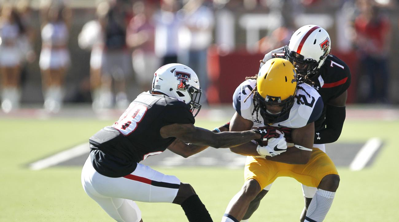 West Virginia wide receiver Ka'Raun White is tackled by Texas Tech defensive backs Paul Banks III, left, and  Jah'shawn Johnson in the first quarter of an NCAA college football game Saturday, Oct. 15, 2016, at Jones AT&T Stadium  in Lubbock, Texas.(Mark R