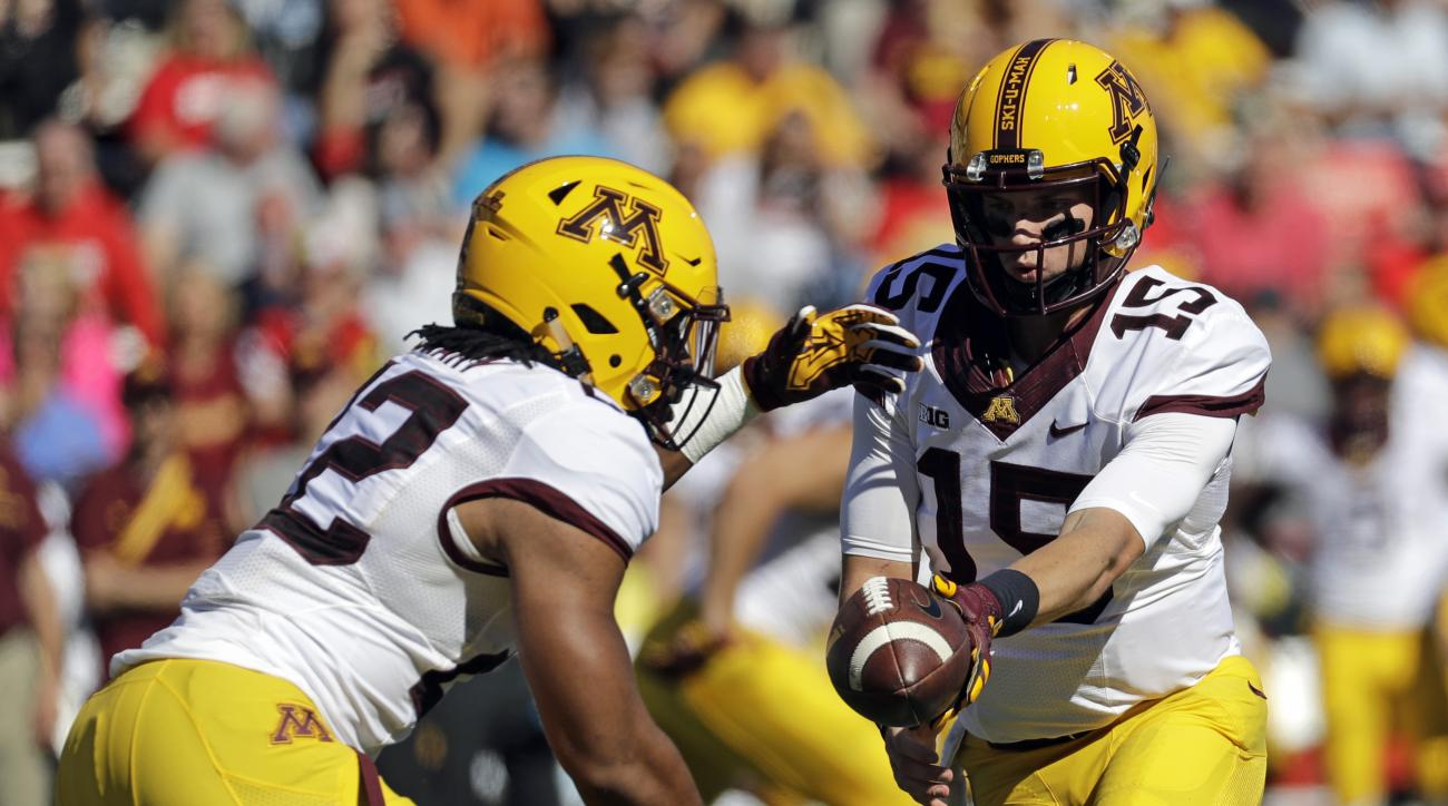 Minnesota quarterback Conor Rhoda, right, hands off the ball to running back Kobe McCrary in the second half of an NCAA college football game against Maryland in College Park, Md., Saturday, Oct. 15, 2016. Minnesota won 31-10. (AP Photo/Patrick Semansky)