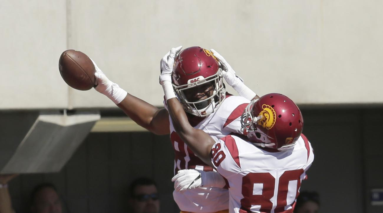 Southern California tight end Daniel Imatorbhebhe (88) celebrates with Deontay Burnett (80) after scoring a touchdown during the first half of an NCAA college football game against Arizona, Saturday, Oct. 15, 2016, in Tucson, Ariz. (AP Photo/Rick Scuteri)