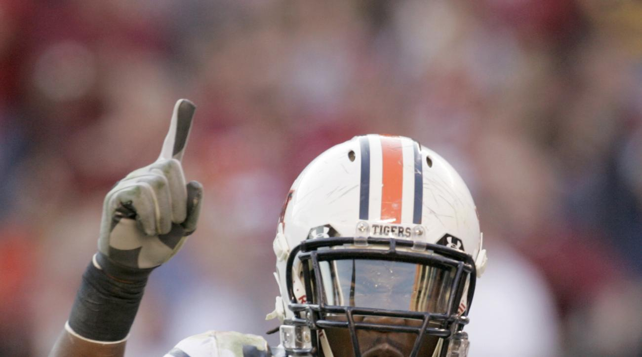 FILE ** In this Nov. 18, 2006 file photo, Auburn's Quentin Groves (54) celebrates after the defense recovered a fumble against Alabama during the first half of a college football game in Tuscaloosa, Ala. Groves, who played defensive end for the Tigers fro