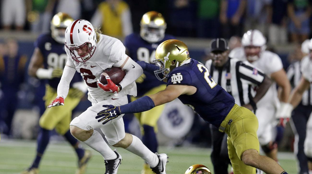 Stanford wide receiver Trenton Irwin (2) leaps over Notre Dame safety Devin Studstill (14) as he's tackled by safety Drue Tranquill (23) during the first quarter of an NCAA college football game in South Bend, Ind., Saturday, Oct. 15, 2016. (AP Photo/Mich