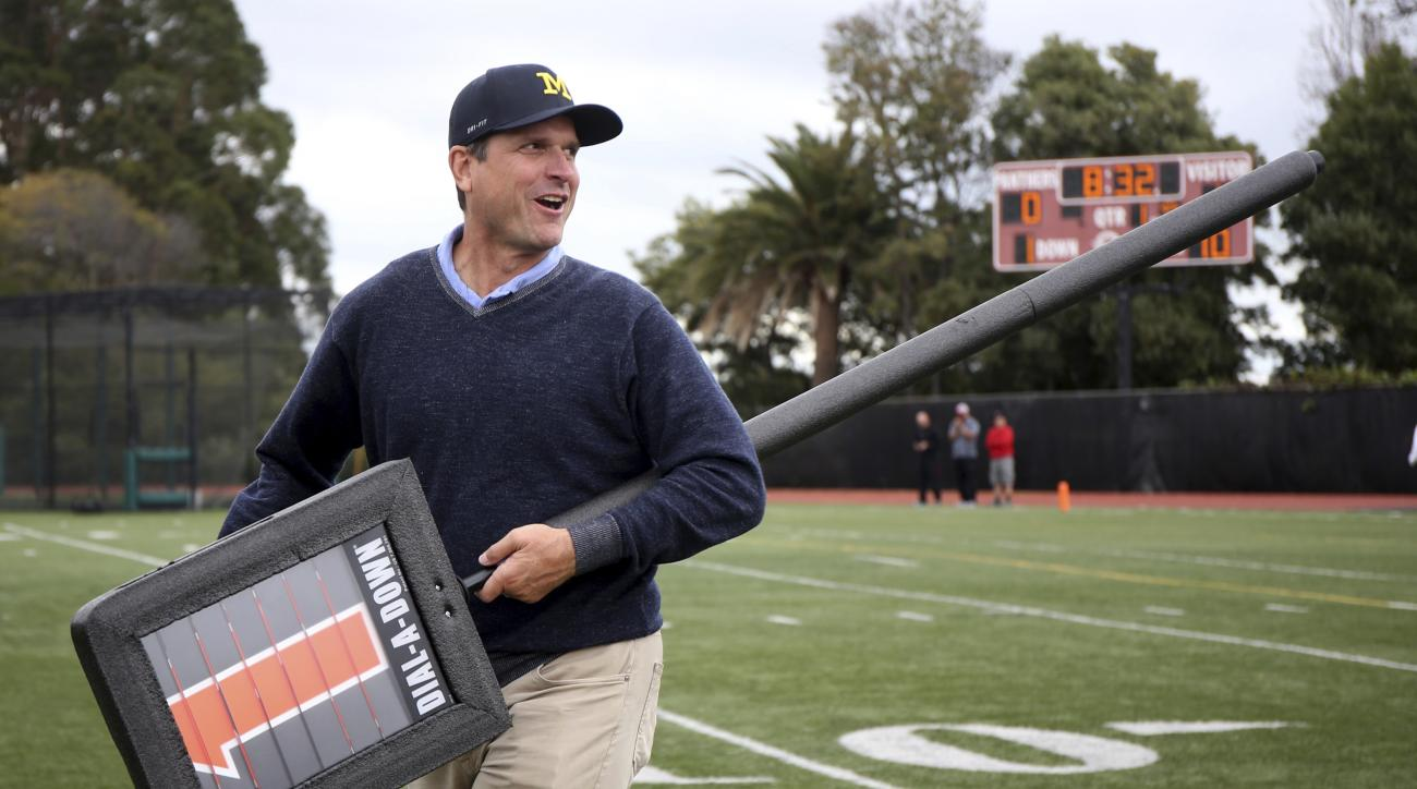 University of Michigan NCAA college football head coach Jim Harbaugh smiles as he carries the down marker on the sideline during the game between El Cerrito and St. Mary's High at St. Mary's High School in Albany, Calif., on Saturday, Oct. 15, 2016. Harba
