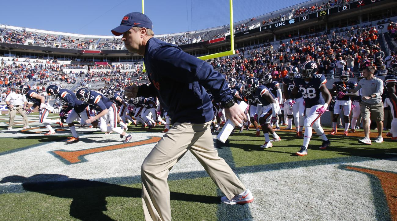Virginia head coach Bronco Mendenhall leads his team onto the field prior to the start of an NCAA college football game between North Carolina and Virginia at Scott stadium in Charlottesville, Va., Saturday, Oct. 22, 2016. (AP Photo/Steve Helber)