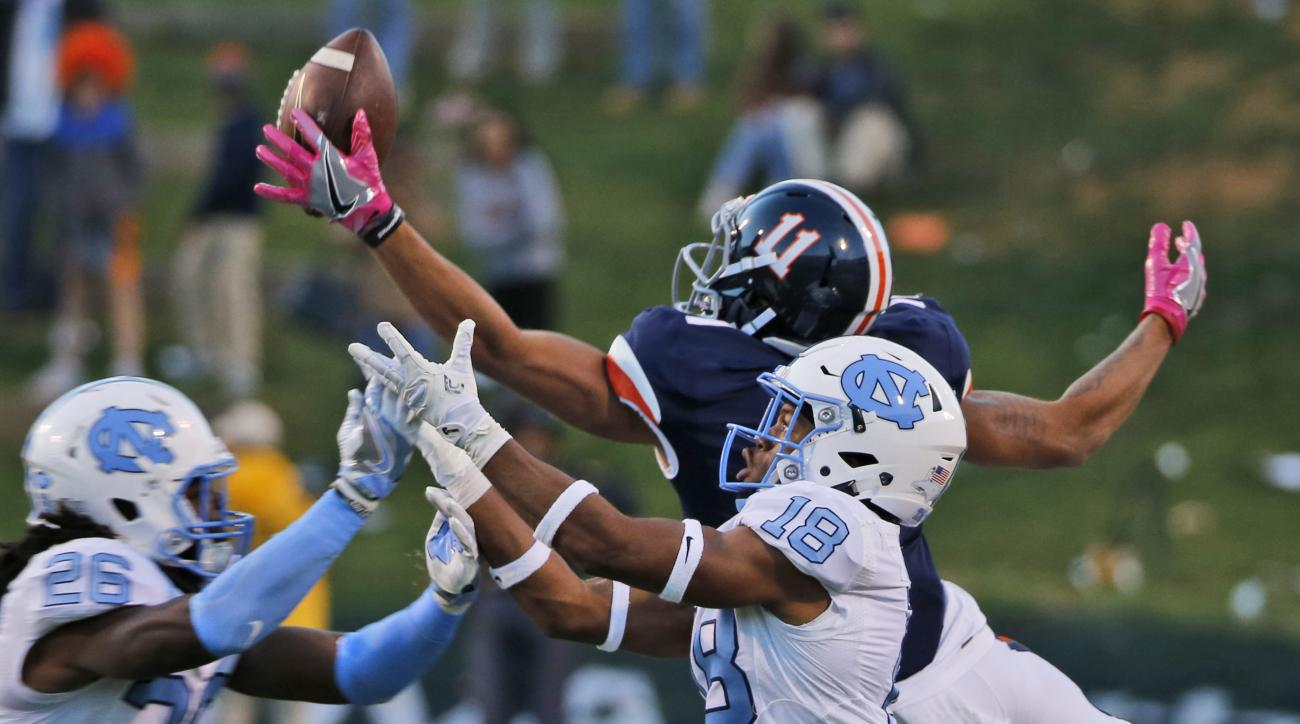 Virginia wide receiver David Eldridge (11) reaches for a pass as North Carolina defensive back Robert Morgan (19) and safety Dominquie Green (26) break up the play during the second half of an NCAA college football game at Scott stadium in Charlottesville