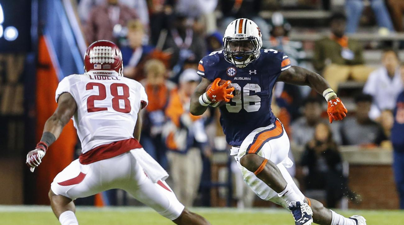 Auburn running back Kamryn Pettway (36) carries the ball as he tries to get around Arkansas defensive back Josh Liddell (28) during the first half of an NCAA college football game, Saturday, Oct. 22, 2016, in Auburn, Ala. (AP Photo/Butch Dill)